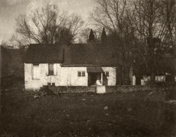 A black and white photograph of the original homestead.