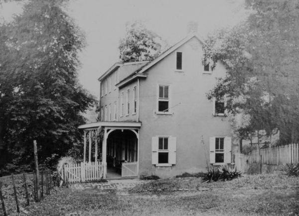 Black and white photograph of a house with a porch.