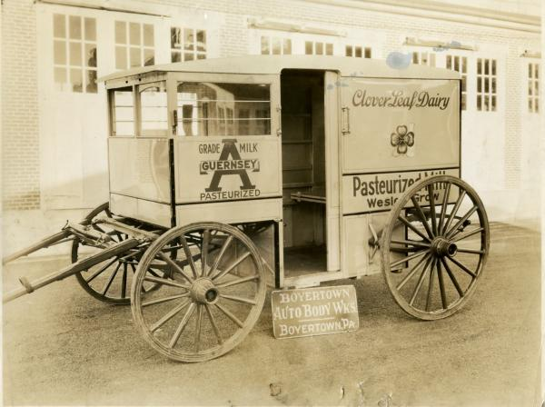 Photograph of a milk wagon. The sign reads Clover Leaf Dairy, Grade A pasteurized milk and the display sign reads, Boyertown Auto Body Works, Boyertown, Pa.
