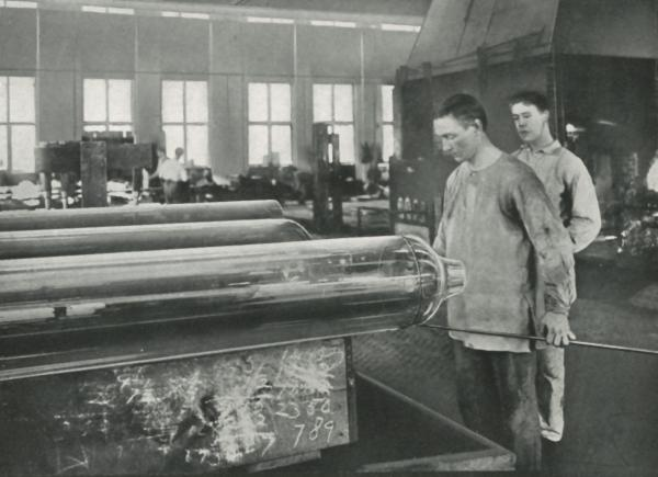 A worker is capping off window glass cylinders preparatory to flattening, while another worker watches.