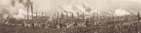 An image of a long line of steam ships docked and a huge crowd in the foreground.