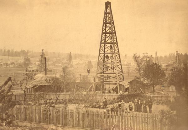 People gather around, on, and near a giant oil derrick.