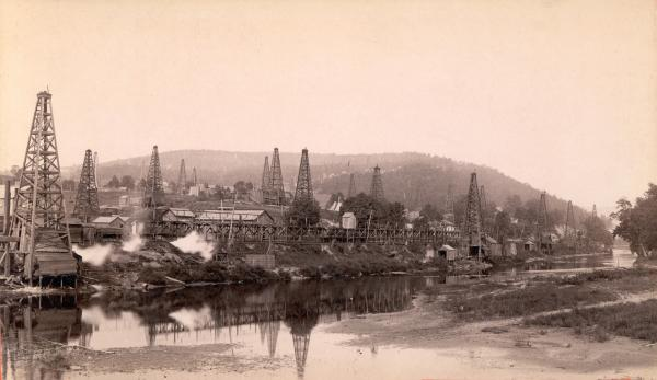 Derricks and homes dot the landscape in this image of an oil town, built along a water way.