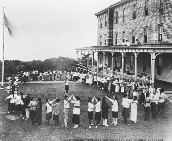 A circle of dancers are on the lawn of the Unity House Lodge.