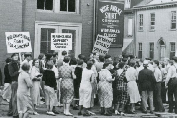 Women walk the picket lines in front of the factory carrying signs that read: Fight for the living wage, Beware Bosses speeches, and Reading Labor Supports Wide Awake Strikers.