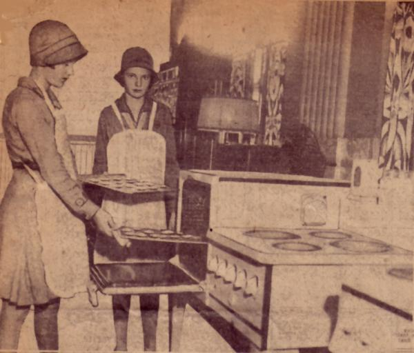 Philadelphia Girl Scouts Virginia Marley and Mildred Meyer baking cookies. One of the girls is removing a tray of cookies from the overn while another watches.