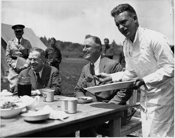 Several official-looking gentlemen are seated around a picnic table about to have lunch. Looking on is a large group of young men. In the background tents are visible.