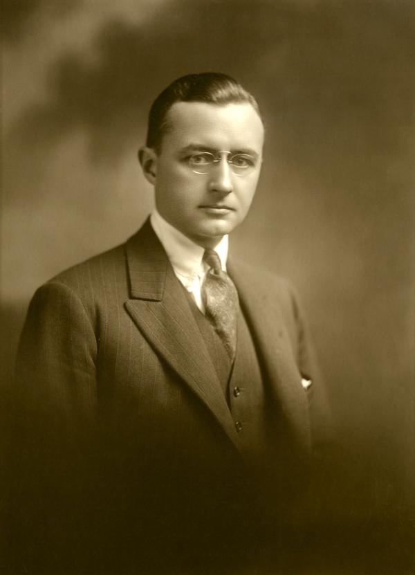 Head and shoulders portrait of Howe, wearing a suit, jacket and vest, dress shirt and tie.
