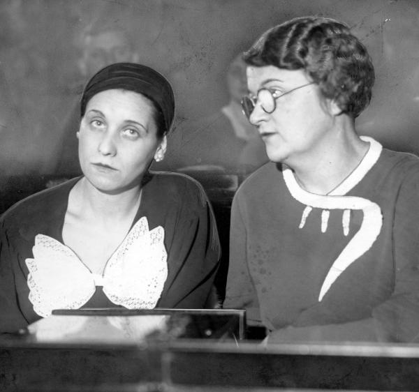 Black and white photograph of two women seated at a desk.