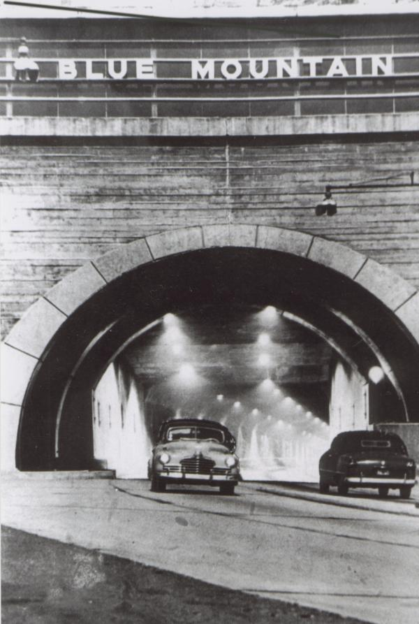 One car exits as another enters a lighted tunnel.