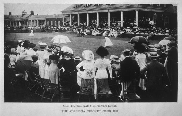 Two females play a match of tennis. The clubhouse is in view in the background and a crowd of spectators can be seen in the foreground.