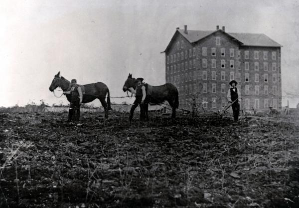 Black and white image of two mules, three students, and the school in the background.