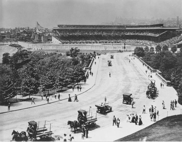 Photograph of the Field in the background and a crowd of people walking, horse drawn wagons and other vehicles stretching far into the foreground on a road that leads to the field.