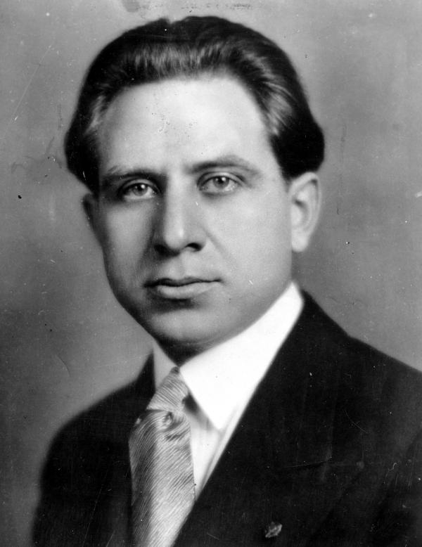 Black and white photograph of a man in a suit and tie; Head shot.