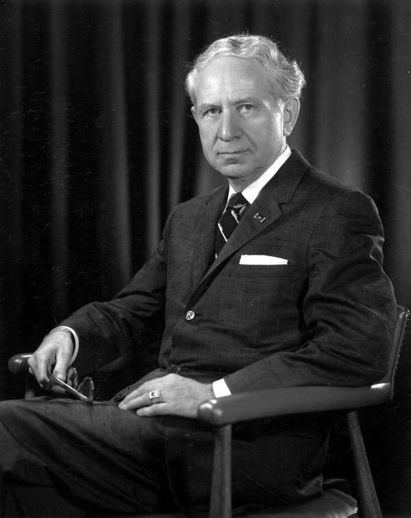 A man seated, wearing a suit and striped tie, holds his glasses in his right hand.