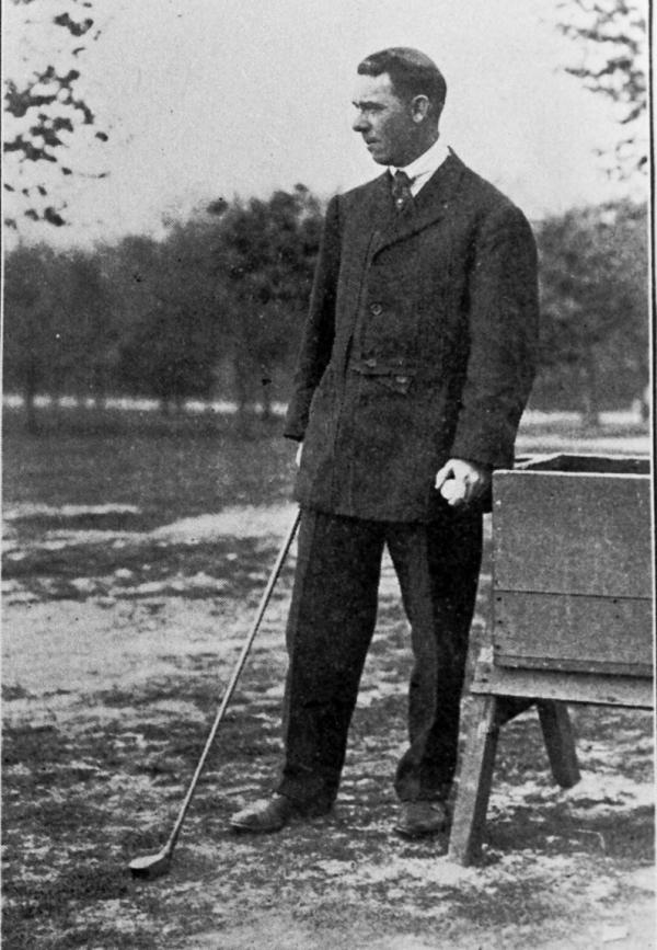 Photograph of a man standing and holding a golf club.