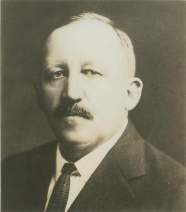Photograph of a man in a suit and tie, head and shoulders.