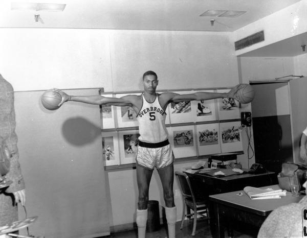 Wilt Chamberlain in uniform, palming two basketballs.