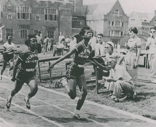 Three runners are shown heading for the finish line. The lead runner, arms outstretched, wins the race. Spectators watch from the sidelines.