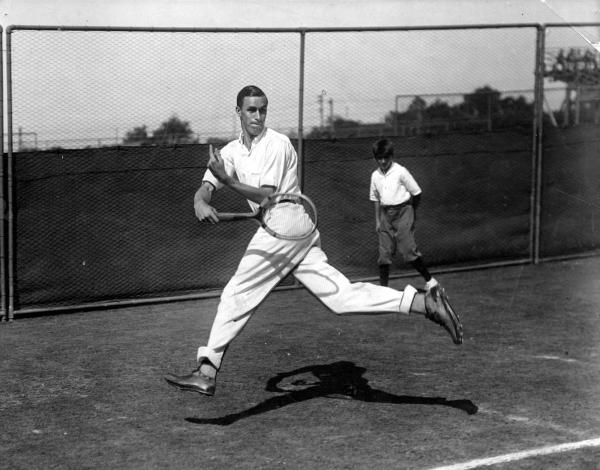 Tennis champion Bill Tilden in motion, stretching  as he hits a return ball with his racket.