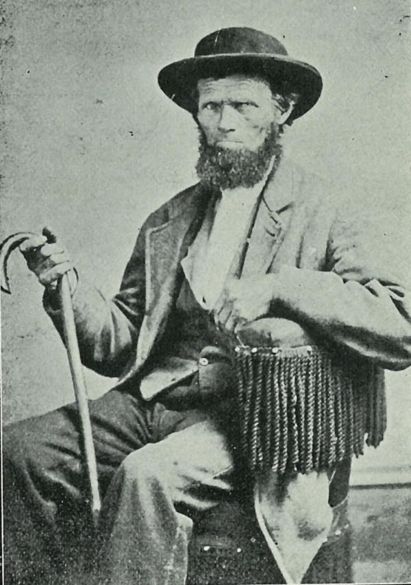 A bearded man wearing a hat and suit, holding a cane, sits in a chair.