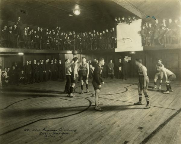 Basketball game in progess in a high school gym.
