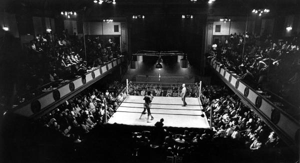 A dark photograph of a huge arena, filled with spectators and in the center is a boxing ring with a boxing match in progress.