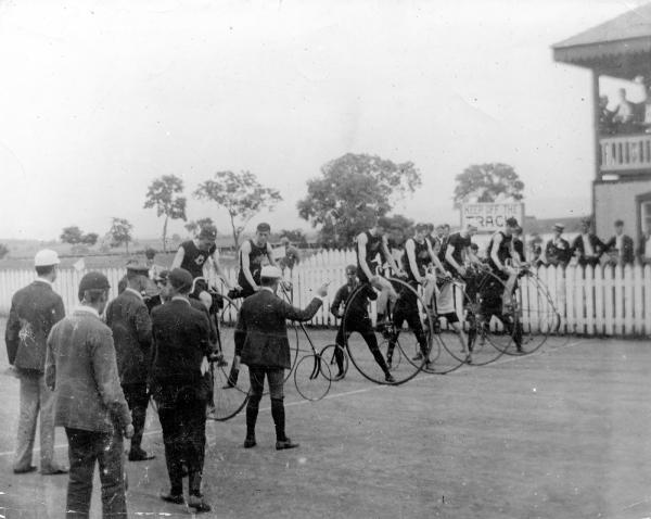 An image of men sitting on all metal high wheeled bicycles are at the starting line. There are spectators in the foreground.