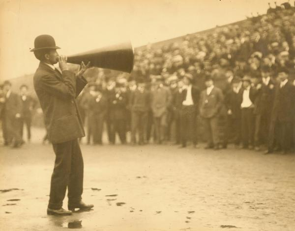 Mike Murphy speaking through megaphone to a crowd at Franklin Field.