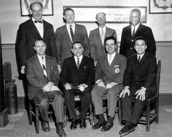 Group photograph of men sitting in chairs.