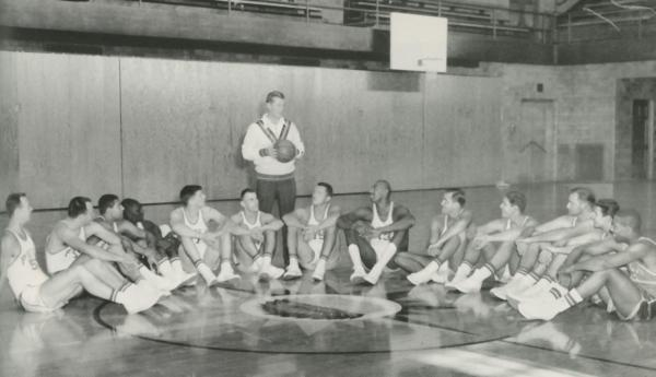 A man wearing a sweater stands, holding a basketball, while a group of young men sit in a semi-circle on a gym floor.