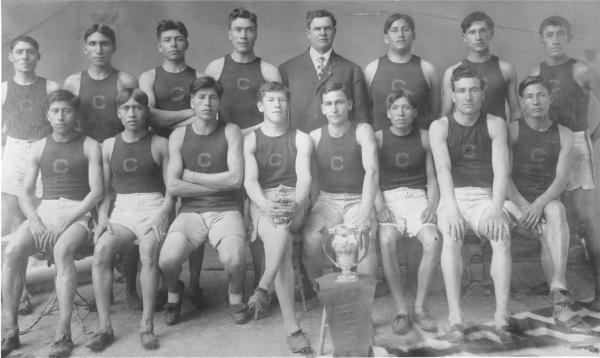 Carlisle Indian School Track Team of 1909, with Coach Warner, a trophy and a pennant that reads Carlisle.