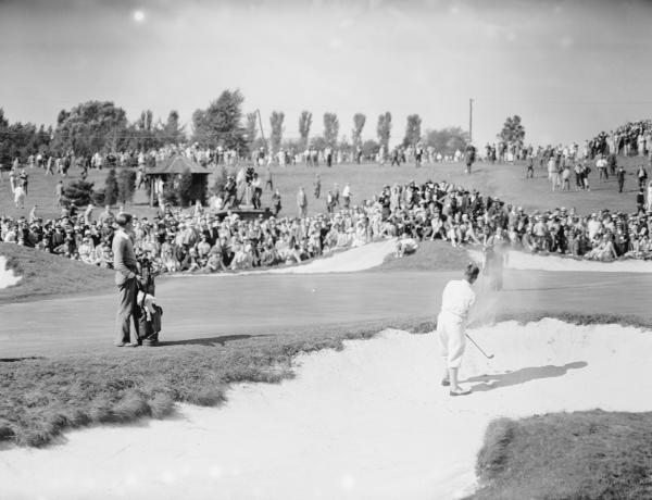A large crowd and a caddy watch as Bobby Jones escapes a sand trap.