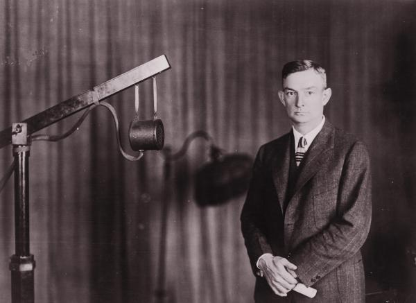 A man wearing a suit and tie, stands next to a microphone.