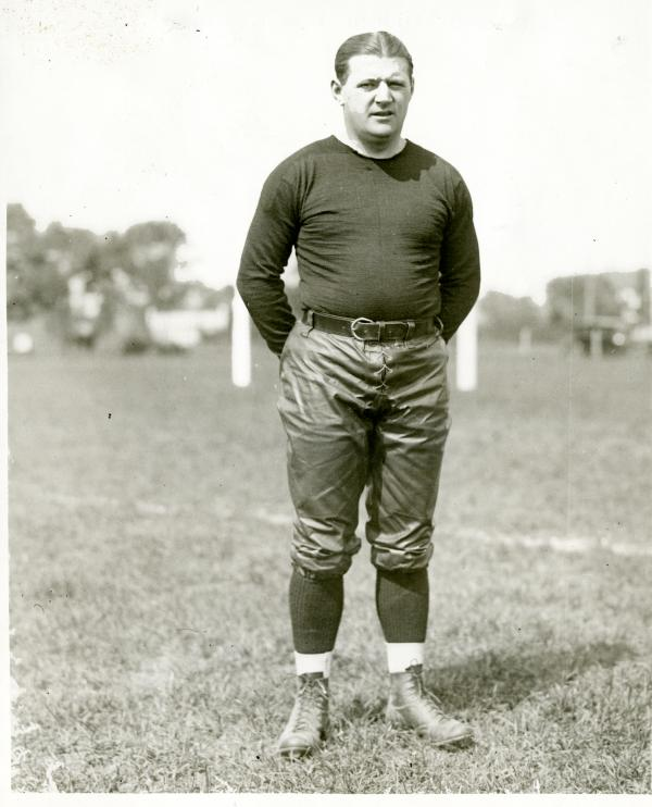 A man in uniform standing on a Ballfield.
