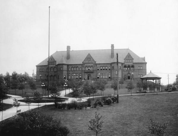 Exterior of a large building, with turrets sitting on taop of a hill.