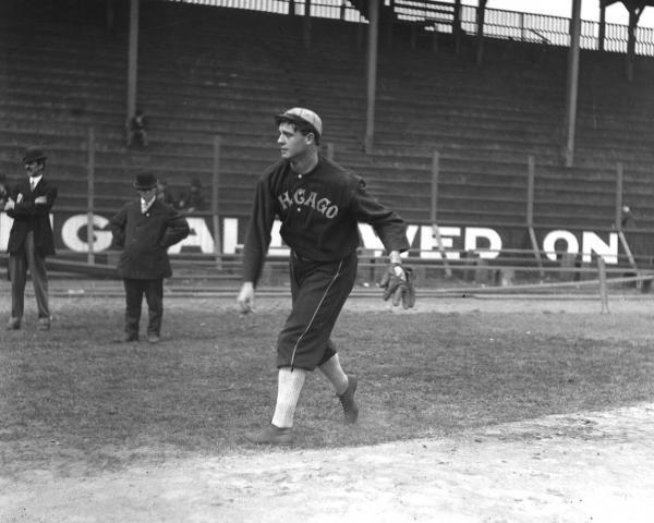 A uniformed baseball player, on the sidelines of the field, warms up for pitching as two men in suits watch. The bleachers in the background are empty save one lone spectator.