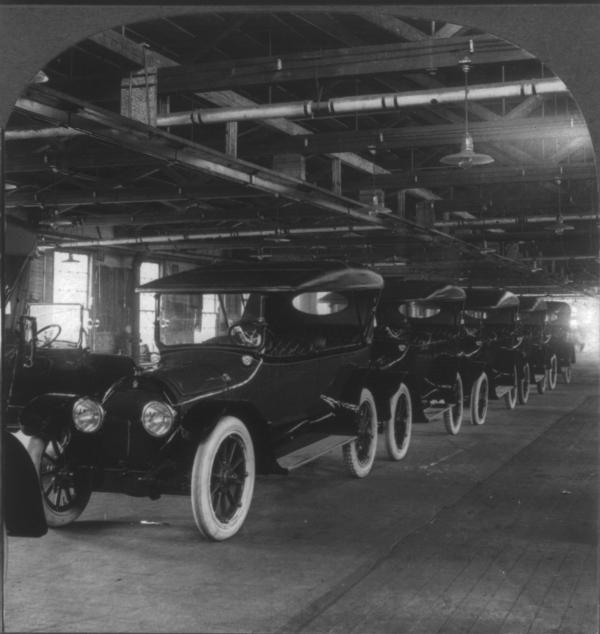 Photographic print on stereo card, stereograph of cars on an assembly line.