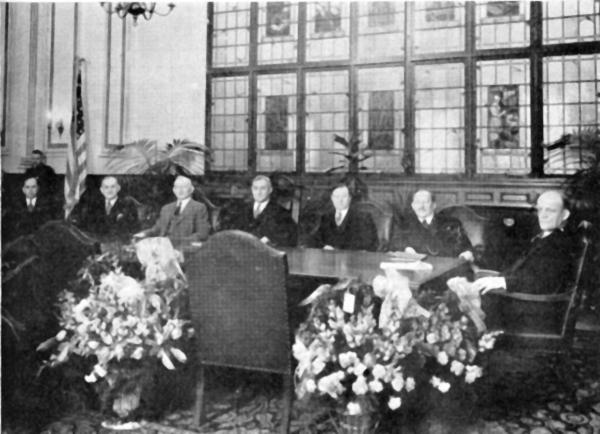 Group photograph of men wearing suits, seated at a conference desk.