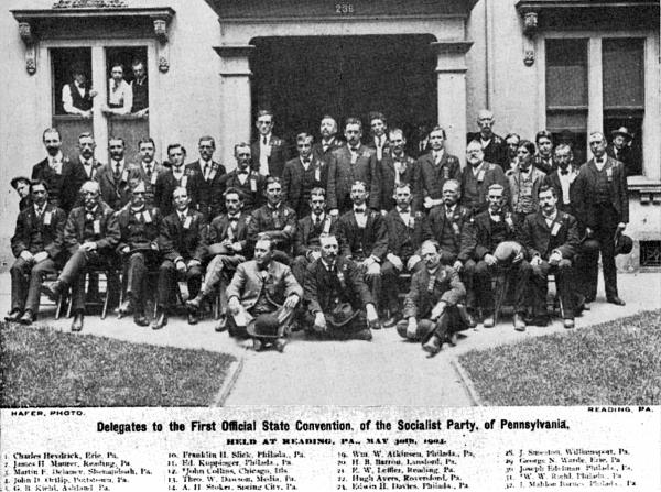 A group of men pose for a photograph, outside, in front of a building. First row of men are seated on the ground, second row are seated in chairs, and the third and fourth rows are standing.