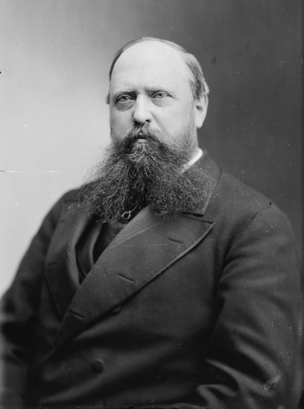 Black and white photograph of a balding, bearded man wearing a suit.