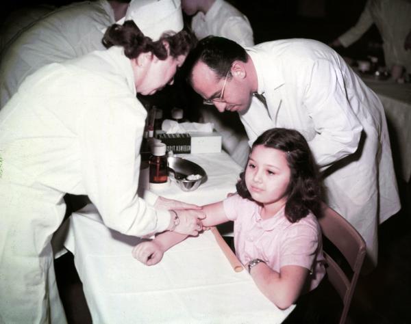 Dr. Jonas E. Salk and a nurse administer a polio vaccine to Pauline Antloger.