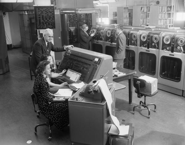 Computer Operators Tabulating the 1954 Census with a UNIVAC Computer. At the computer instrument panel are (front to back) Clydia Beeps, Maxine C. Warner, and the Deputy Director of the Bureau of Census, A. Ross Echler