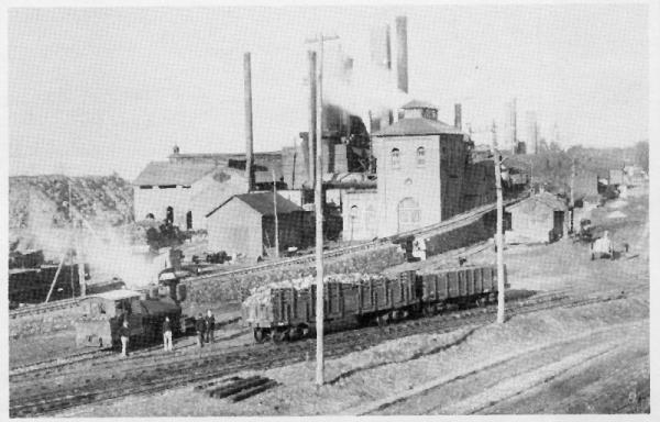 In this black and white photograph an iron factory sits in the middle, in the background one can make out ore banks, and in the foreground railroad tracks with a train caboose and a couple of rail car loads of iron ore. Four men stand nearby the train on the tracks.