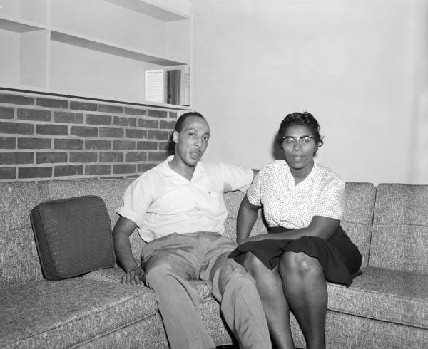 A man and a woman are seated on a couch.