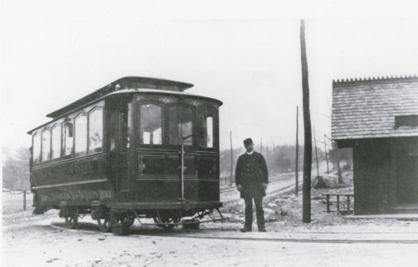 A man stands next to a trolley.
