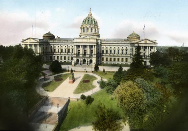 The State Capitol building with landscaped area in front. A monument in the middle is surrounded by landscaped area and many lush trees.