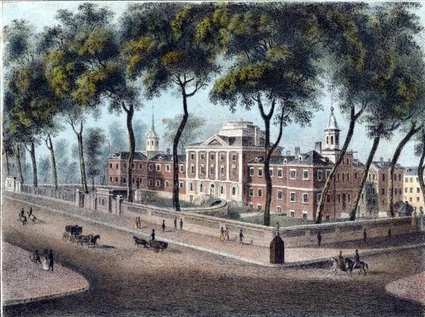 Exterior view of the hospital, located on Pine Street between 8th and 9th Streets, from the southeast. Street scene in foreground includes a carriage; a wagon; several riders on horseback including a woman riding side saddle; pedestrians; and a watchman's guardhouse. Designed by Samuel Rhoads and David Evans, Jr., the east wing of the hospital was constructed 1755, the west wing and center pavilion in the 1790s.