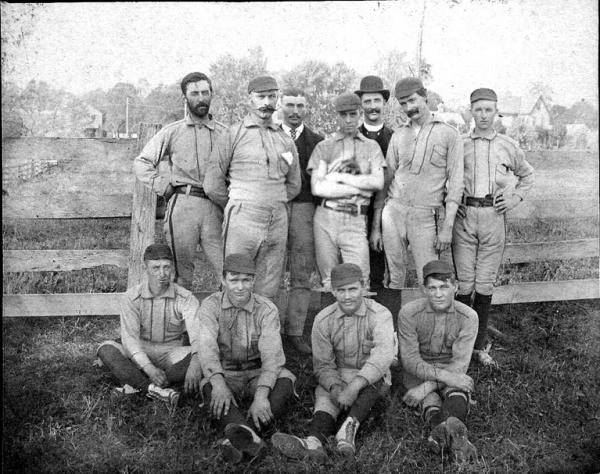 Mike Grady, is seated far right.  The players are: Henry Whitacre – Pitcher, Jack Thompson – Catcher,