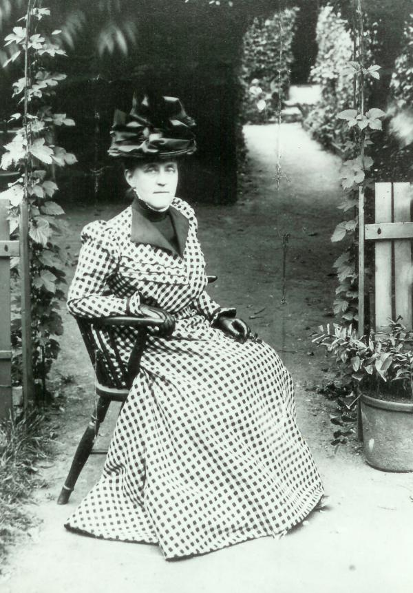 Black and white photograph of Mira Lloyd Dock in checkered dress, black hat, and gloves, sitting in a back yard or garden.